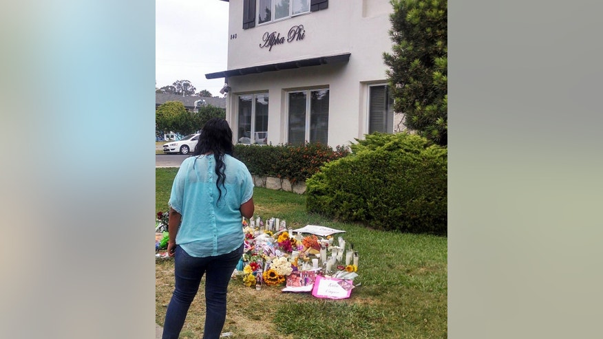 A woman views a sidewalk memorial for Katie Cooper and Veronica Weiss, two of the victims of a shooting rampage by Elliott Rodger, outside the Delta Phi sorority house in the Isla Vista neighborhood of Goleta, Calif., Monday, May 26, 2014. Six people, all students at nearby University of California, Santa Barbara, were killed before Rodger was killed by gunfire in the 10-minute rampage Friday, May 23. (AP Photo/Christopher Weber)