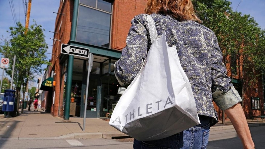 In this photo taken May 14, 2014, Jody Dickman, of Pittsburgh walks in the Shadyside section of Pittsburgh after shopping for a workout outfit at an Athleta store. The private Conference Board reports on consumer confidence for May on Tuesday, May 27, 2014. (AP Photo/Gene J. Puskar)