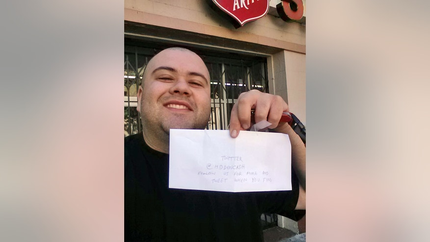 May 25: This image provided by Sergio Loza shows Loza holding up an envelope that had cash hidden in it in San Francisco. Loza followed the clues from a Twitter user using the handle @HiddenCash to find the money.
