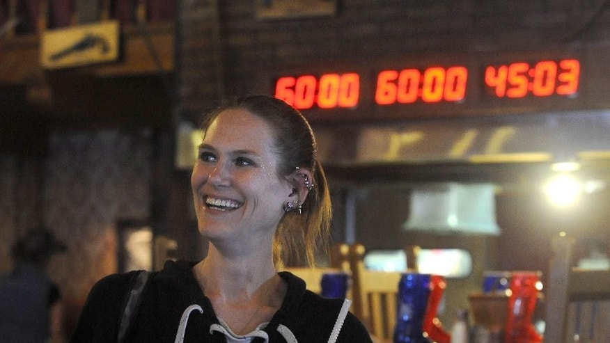 In this  photo taken Monday, May 26, 2014, Molly Schuyler, of Bellevue, Neb., smiles after eating two 72-ounce steak meals in under 15 minutes at The Big Texan Steak Ranch in Amarillo, Texas. The competitive eater set a record. The countdown time of 45:03 means she finished both meals in 14 minutes, 57 seconds. (AP Photo/The Amarillo Globe News, Sean Steffen)