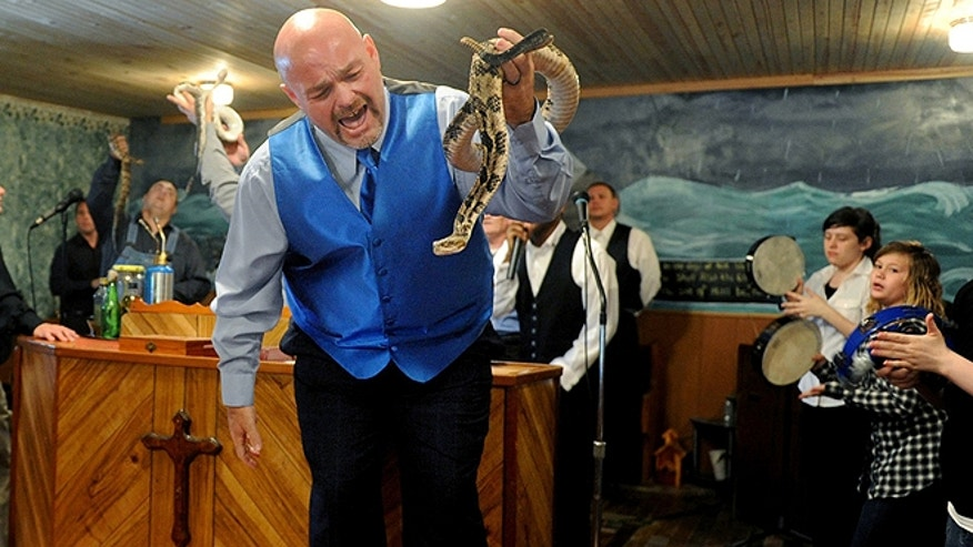 May 6, 2012: Jamie Coots, pastor of the Full Gospel Tabernacle in Jesus Name Church of Middlesboro, Ky., stands on a bench before the church, singing and holding a rattlesnake during service at Tabernacle Church of God in LaFollette, Tenn. Coots died Feb. 16 after being bitten by a rattlesnake. (AP/The Tennessean, Shelley Mays)