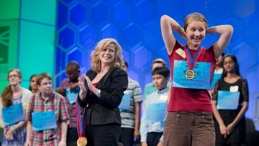 Eighth grade home-schooled student Kate Miller, 14, of Abilene, Texas, right, celebrates after making it to the finals of the Scripps National Spelling Bee, Thursday, May 29, 2014, at National Harbor in Oxon Hill, Md. Applauding in the center is Paige Kimble, executive director of the Scripps National Spelling Bee.   (AP Photo/Manuel Balce Ceneta)