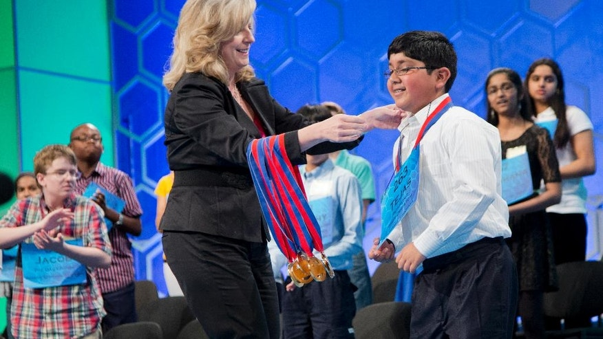 Finalist Tejas Muthusamy, right, 11, of Glen Allen, Va., is congratulated by Paige Kimble, executive director of the Scripps National Spelling Bee, left, after awarding him his medal, during the Scripps National Spelling Bee, Thursday, May 29, 2014, at National Harbor in Oxon Hill, Md.  (AP Photo/Manuel Balce Ceneta)