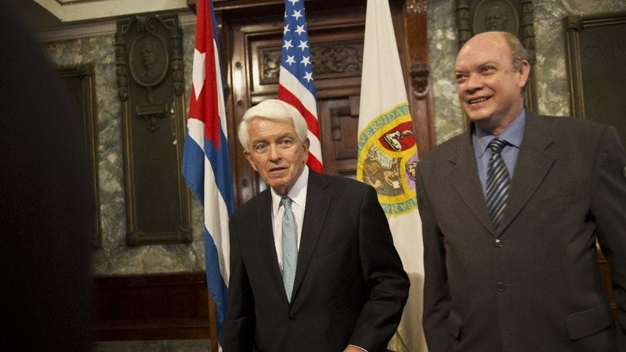 U.S. Chamber of Commerce President and CEO Thomas Donohue, left, and Cuba's Minister of Foreign Trade and Commerce Rodrigo Malmierca Diaz walk in front of the Cuban and US flags after a conference at the auditorium of the University in Havana, Cuba, Thursday, May 29, 2014. Donahue urged Cuba to deepen economic reforms on the island, and the US to take steps to normalize relations with the Caribbean nation. (AP Photo/Ramon Espinosa)