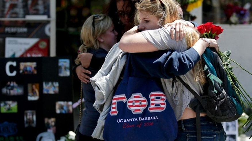 May 27, 2014: Mourners hug in front of the IV Deli Mart, where part of Friday night's mass shooting took place in the Isla Vista area near Goleta, Calif.
