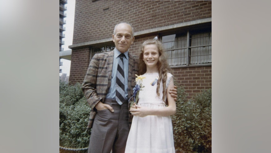 In this June 1971 photo provided by Beth J. Harpaz, Beth is shown as a child after her graduation from elementary school in New York, with her father, David Jackendoff. Jackendoff parachuted into Normandy with the 101st Airborne on D-Day, June 6, 1944. Though he died in 1993, wartime radio interviews with him and a TV interview on the 40th anniversary of D-Day preserved his stories. (AP Photo/Courtesy of Beth J. Harpaz)