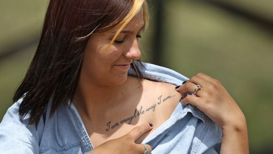 May 29: Wasatch High School sophomore Shelby Baum, 16, points to her tattoo. A group of Utah high school students, including Baum, said they were shocked and upset to discover their school yearbook photos were digitally altered.
