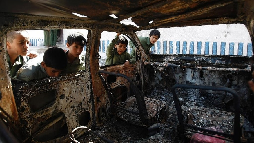 FILE – This May 27, 2014, file photo shows Yemeni boys looking at a vehicle destroyed during a police raid on an al-Qaida militants' hideout in the Arhab region, north of Sanaa, Yemen, which resulted in the death of five militants and six soldiers. According to the Obama administration's most recent terrorism report, released by the State Department in late April, al-Qaida's core leadership has been degraded, limiting its ability to launch attacks and lead its followers. This has resulted in more autonomous and more aggressive affiliates, notably in Yemen, Syria, Iraq, northwest Africa and Somalia, according to the report, which recorded a 43 percent increase in terrorist attacks worldwide from 2012 to 2013. (AP Photo/Hani Mohammed)