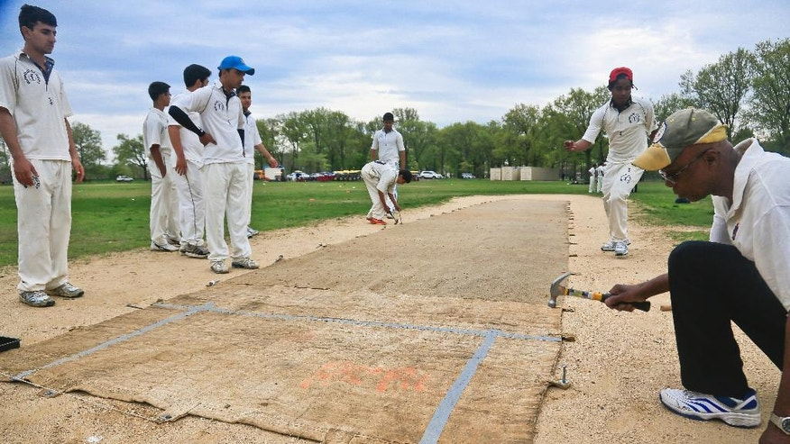 In this May 12, 2014 photo, a sand and gravel cricket pitch is covered with a mat being hammered into the ground before a cricket match between Public School Athletic League (PSAL) teams John Adams and Midwood high schools, at Marine Park in the Brooklyn borough of New York. While not a feature in the professional game, a mat overlay is common for amateur matches, providing a smooth playing surface on the 22-yard pitch, where batters and bowlers contest the game for runs and outs respectively. (AP Photo/Bebeto Matthews)