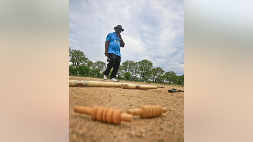 In this May 12, 2014 photo, cricket umpire Carl Whatley walks with a hammer as he approaches stump poles, center, and bails, foreground, which he will use to construct a wicket for a Public School Athletic League (PSAL) cricket match between John Adams and Midwood high schools at Marine Park in the Brooklyn borough of New York. The wicket - three wooden stump poles set upright into the ground, and topped with two wooden crosspieces known as the bails - is defended by a batsman who attempts to prevent the ball from hitting the wicket by hitting the ball first to score runs. (AP Photo/Bebeto Matthews)