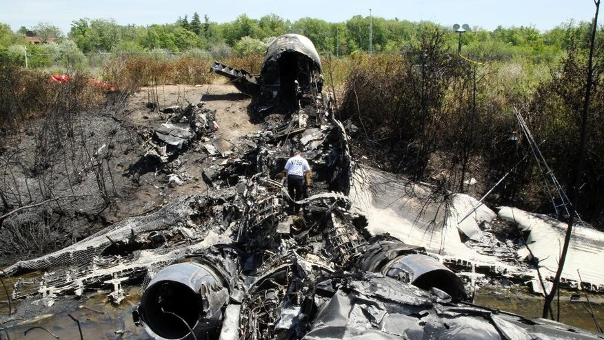 June 2, 2014: A National Transportation Safety Board official looks through the wreckage at the scene in Bedford, Mass., where a plane plunged down an embankment and erupted in flames during a takeoff attempt at Hanscom Field Saturday night. (AP)