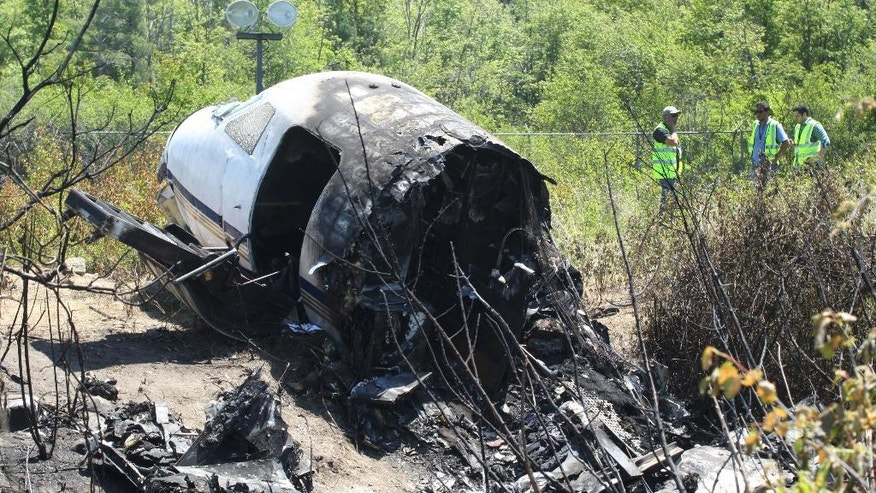 Officials work near wreckage at the scene Monday, June 2, 2014, in Bedford, Mass., where a plane plunged down an embankment and erupted in flames during a takeoff attempt at Hanscom Field on Saturday night. Lewis Katz, co-owner of The Philadelphia Inquirer, and six other people died in the crash. (AP Photo/Boston Herald, Mark Garfinkel, Pool)