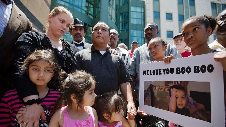 Alecia and Boun Khan Phonesavanh, from rear left, the parents of 19-month-old Bounkham Phonesavanh who was severely burned by a flash grenade during a SWAT drug raid, attend a vigil with their daughters outside Grady Memorial Hospital where he is undergoing treatment, Monday, June 2, 2014, in Atlanta. A Georgia state senator says he will ask U.S. Attorney Sally Quillian Yates to investigate a police raid where the Georgia toddler was severely burned by a flash grenade. State Sen. Vincent Fort joined 19-month-old Bounkham Phonesavanh's family at a prayer vigil outside Grady Memorial Hospital in Atlanta on Monday. The boy's mother says a fever may delay a planned surgery. Police have said officers were looking for a suspect who may have been armed and didn't know children were inside. (AP Photo/David Goldman)
