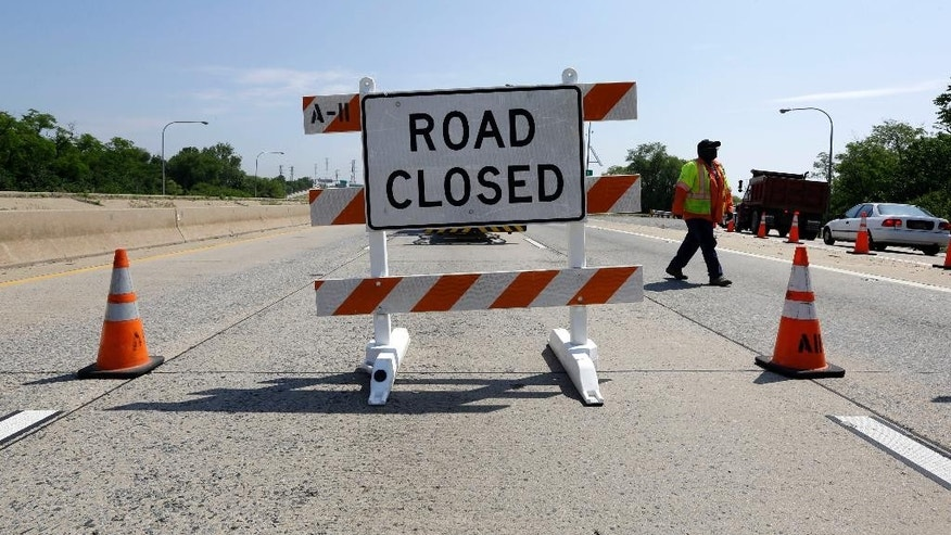 A worker with Delaware Department of Transportation walks behind a warning sign on Interstate 495 near Wilmington, Del., Tuesday, June 3, 2014, after it was closed due to the discovery of four tilting support columns on a bridge over the Christina River. The closure created heavier-than-normal traffic conditions for motorists on Interstate 95, a major East Coast artery. The bridge normally carries about 90,000 vehicles a day. (AP Photo/Patrick Semansky)