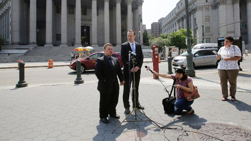Bryan Ellicott, left, speaks at a news conference in front of State Supreme Court, Tuesday, June 3, 2014 in New York. The transgender man has sued New York City after he says he was booted from a male locker room at a public pool in Staten Island. He says a staff member ordered him to use the women's locker room. Joining him at the microphones is Michael Silverman, Executive Director of the Transgender Legal Defense & Education Fund. (AP Photo/Mark Lennihan)