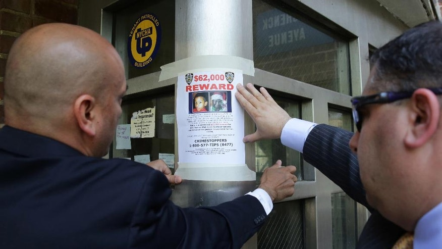 Members of the New York Police Department affix a reward poster at an entrance to the Boulevard Houses in the Brooklyn borough of New York on Wednesday, June 4, 2014. On Sunday evening, two children were stabbed at housing complex. Six-year-old Prince Joshua Avitto, at left in poster, was killed, and 7-year-old Mikayla Capers was critically injured.(AP Photo/Peter Morgan)