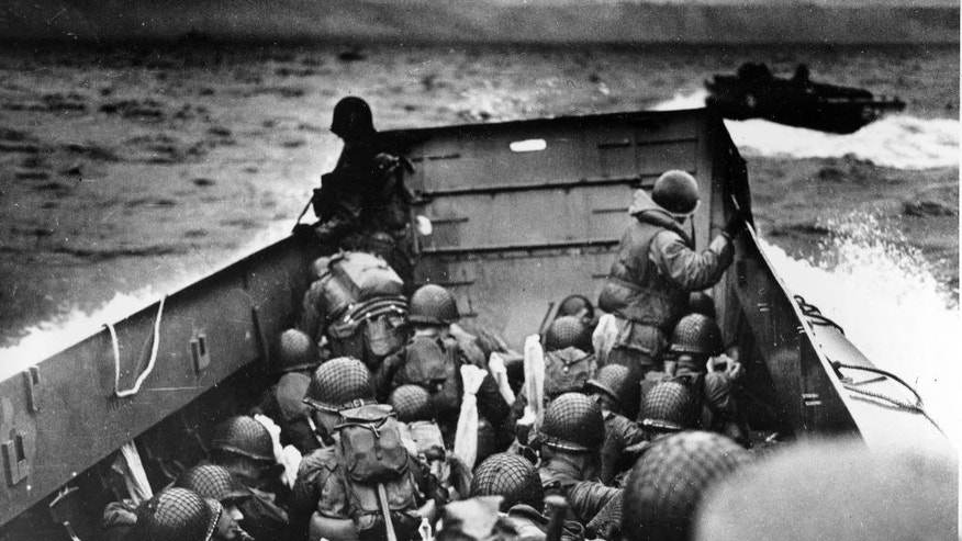 """FILE - In this June 6, 2014 file photo, allied troops crouch behind the bulwarks of a landing craft as it nears Omaha Beach during a landing in Normandy, France. The D-Day invasion broke through Adolf Hitler's western defenses and led to the liberation of France from Nazi occupation just as the Soviet Army was making advances in the east, turning the tide of the war in the Allies' favor.  Allied troops landed on the Normandy coast of France in tremendous strength by cloudy daylight today and stormed several miles inland with tanks and infantry in the grand assault which Gen. Dwight D. Eisenhower called a crusade in which """"we will accept nothing less than full victory.""""(AP Photo/U.S. Coast Guard, File)"""