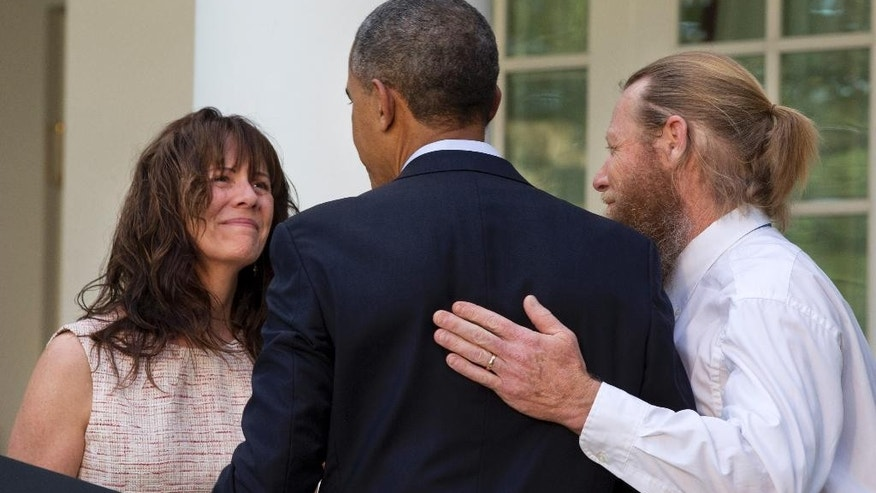 FILE - This May 31, 2014 file photo shows the parents of U.S. Army Sgt. Bowe Bergdahl, Jani Bergdahl, left, and Bob Bergdahl, turn to President Barack Obama after he spoke in the Rose Garden of the White House in Washington, Saturday, May 31, 2014, after the announcement that Bowe Bergdahl has been released from captivity in Afghanistan. Bergdahl, 28, had been held prisoner by the Taliban since June 30, 2009. He was handed over. That feel-good moment in the Rose Garden sure seems like a long time ago. Just a week after the president announced that Sgt. Bowe Bergdahl had been freed in Afghanistan, details emerging about the soldier, the deal and how the rescue came together are only adding to the list of questions. A look at what's known _ and unknown _ about saving Sgt. Bergdahl.  (AP Photo/Jacquelyn Martin, File)