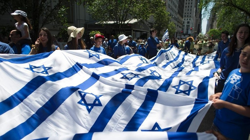 FILE - In this Sunday, June 1, 2014 file photo, revelers carry a banner made of Israeli flags as they march up Fifth Avenue during the Celebrate Israel Parade. Once a unifying cause for generations of American Jews, Israel is now bitterly dividing Jewish communities. (AP Photo/John Minchillo)