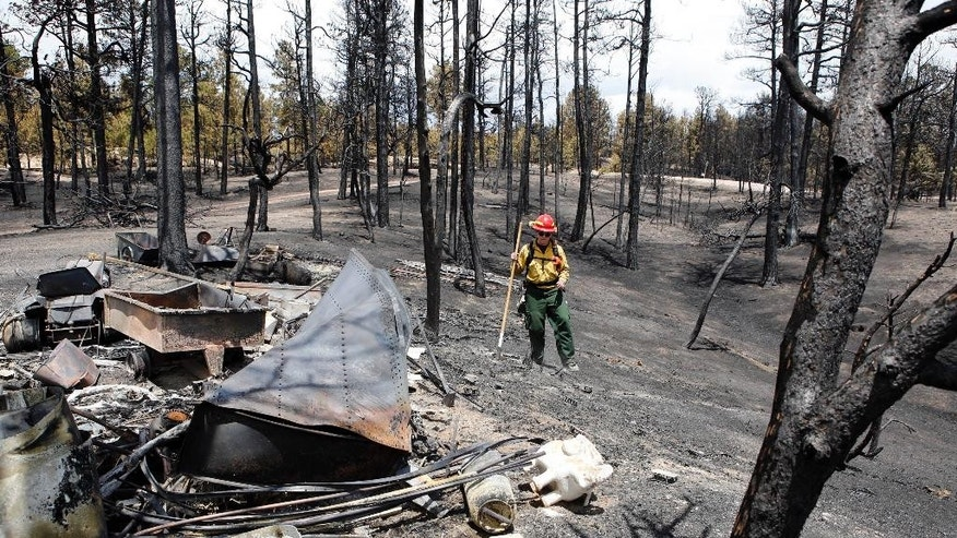 FILE - In this June 2013 file photo, firefighter Brandie Smith from Salida, Colo., walks past a burned out structure at the Black Forest wildfire north of Colorado Springs, Colo.  Sheriff Terry Maketa is set to release an after-action report on the Black Forest Fire Tuesday morning, June 10, 2014,. The fire started a year ago this week. It destroyed nearly 500 houses and killed two people north of Colorado Springs. (AP Photo/Ed Andrieski, File)