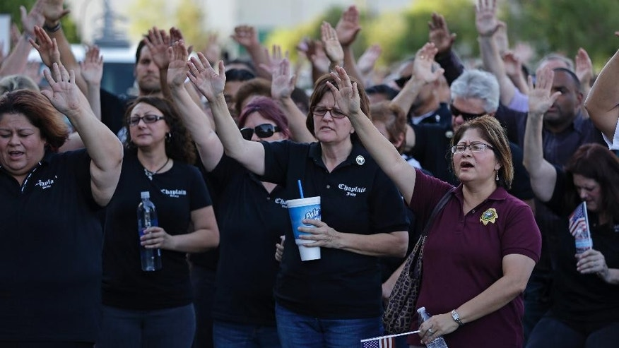 People pray during a vigil at CiCi's Pizza Monday, June 9, 2014 in Las Vegas. The vigil was held to honor two Las Vegas Metropolitan Police officers and a bystander who were killed Sunday. (AP Photo/John Locher)