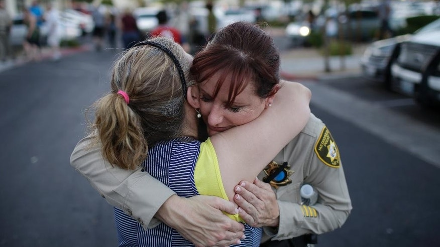 Cheri Rasmussen, left, embraces Las Vegas Metropolitan Police Lt. Roxanne McDaris after a vigil near CiCi's Pizza Monday, June 9, 2014 in Las Vegas. The vigil was held to honor two Las Vegas Metropolitan Police officers and a bystander who were killed Sunday at a strip mall. (AP Photo/John Locher)