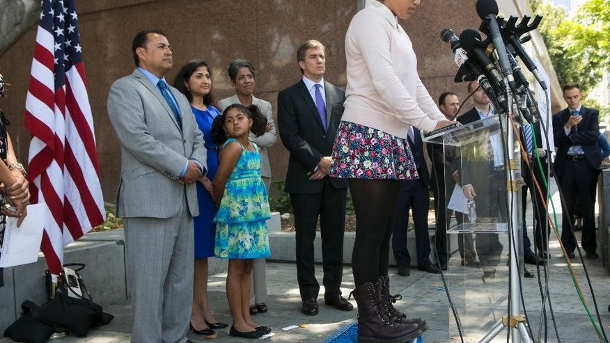 Student Julia Macias, right at lectern, a plaintiff and Los Angeles Unified School District Middle School, comments on the Vergara v. California lawsuit verdict in Los Angeles, Tuesday, June 10, 2014. Others from left, parents, Joe Macias, with wife, Evelyn, and their daughter Lucy, Russlyn Ali, Former Assistant Secretary of U.S. Education Department Office for Civil Rights, and Students Matter Board member, with Founder David Welch. (AP Photo/Damian Dovarganes)