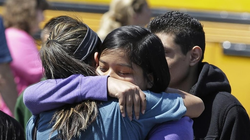 Sutdents embraces with family members after arriving at a shopping center parking lot in Wood Village, Ore., after a shooting at Reynolds High School Tuesday, June 10, 2014, in nearby Troutdale. A gunman killed a student at the high school east of Portland Tuesday and the shooter is also dead, police said. (AP Photo/Rick Bowmer)