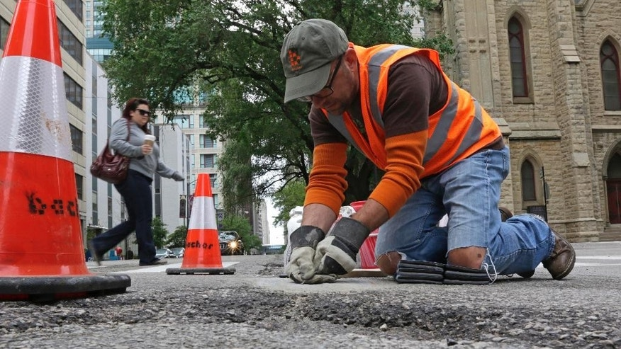 In this Tuesday, June 10, 2014 photo, mosaic artist Jim Bachor scrapes cement off a finished art piece on a street in Chicago. Bachor has filled seven potholes around the city and marks each one with a mosaic piece. (AP Photo/Stacy Thacker)