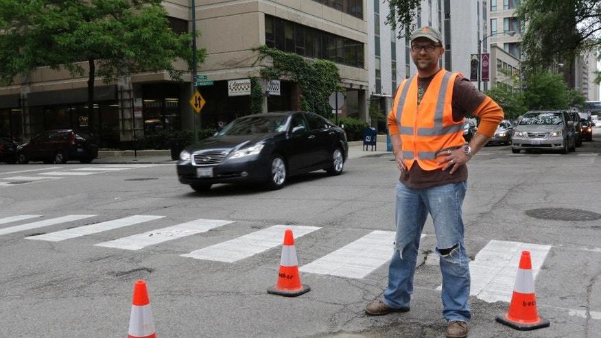 In this Tuesday, June 10, 2014 photo, mosaic artist Jim Bachor,poses next to his finished public art project on a street near downtown Chicago. Bachor has filled seven potholes around the city and marks each one with a mosaic piece. (AP Photo/Stacy Thacker)