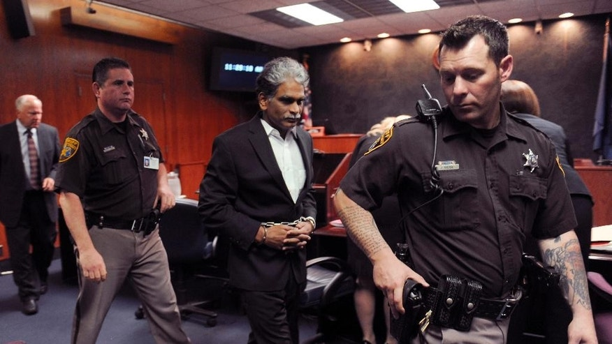 Lakshminivasa Nerusu is lead off to jail by two Oakland County Sheriff Deputies after a guilty verdict in Pontiac, Mich. on Thursday, June 12 2014.  Nerusu, who fled to India after the 2008 slayings of his wife and two children in their suburban Detroit home has been convicted of first-degree murder in their deaths.  Thirty-seven-year-old Jayalakshmi  Nerusu, the couple's 14-year-old daughter Tejasvi and their 12-year-old son Siva, were killed Oct. 13, 2008. Police in Novi checking on the family's welfare found their bludgeoned bodies two weeks later. (AP Photo/Detroit News, Charles V. Tines)  DETROIT FREE PRESS OUT; HUFFINGTON POST OUT