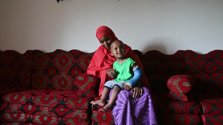 Fadumo Abudllahi holds her son Musa, 16, months, at their home Wednesday, June 11, 2014 in Minneapolis. Musa Dayib survived an 11-story fall from their home in a Minneapolis high-rise a month ago.  Doctors will remove his last cast Thursday, the one covering his left arm from the wrist to the biceps. The only other visible sign of his fall is a pink scar on the back of his head.  (AP Photo/The Star Tribune, David Joles)  MANDATORY CREDIT&#x3b; ST. PAUL PIONEER PRESS OUT&#x3b; MAGS OUT&#x3b; TWIN CITIES TV OUT