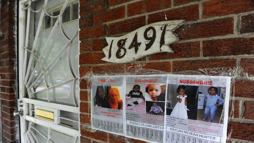 Flyers of a missing woman and children are taped to the brick home of Alicia Fox, Tuesday, June 10, 2014, in Detroit. Police and the FBI are searching for two young Detroit siblings, 6-year-old Kaylah Hunter and 6-month-old brother, Kristian Justice, after their 27-year-old mother was found shot to death in a vacant house about six miles from her home. No suspects have been identified. (AP Photo/Detroit News, David Coates) DETROIT FREE PRESS OUT; HUFFINGTON POST OUT.