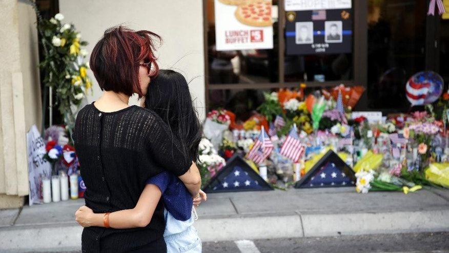 Hieu Le, left, kisses her nine-year-old daughter Allie Le while visiting a makeshift memorial at a CiCi's Pizza, Tuesday, June 10, 2014, in Las Vegas. The attack Sunday at the restaurant killed officers Alyn Beck, 41, and Igor Soldo, 31, both of whom were husbands and fathers. (AP Photo/John Locher)