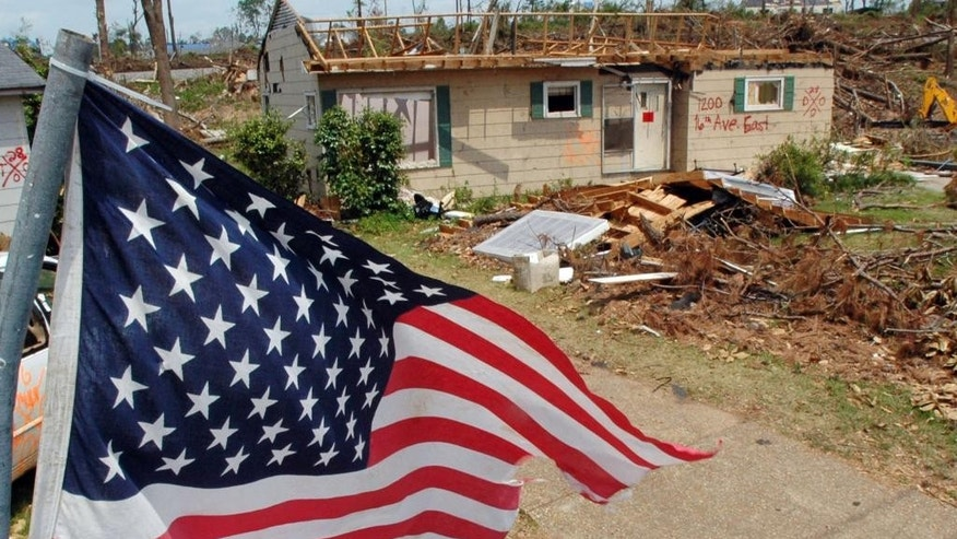 FILE - This May 23, 2011 file photo shows an American flag flying over the remains of a tornado-ravaged neighborhood in Tuscaloosa, Ala., a month after a killer storms in Alabama. Oklahoma and Kansas may have the reputation as tornado hotspots, but Florida and the rest of the Southeast are far more vulnerable to killer twisters, a new analysis shows. (AP Photo/Jay Reeves, File)