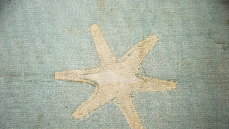 In this Thursday, June 5, 2014 photo shown is a star on the recently conserved George Washington's flag, which flew to denote his presence at various battles during the war against Britain, at the Museum of the American Revolution's facility near Philadelphia. The small banner, now a faded blue with 13 white six-pointed stars, is among thousands of objects waiting for a permanent home at the soon-to-be-built Revolution museum.  (AP Photo/Matt Rourke)