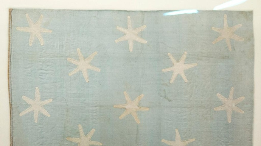 In this Thursday, June 5, 2014 photo shown is the recently conserved George Washington's flag, which flew to denote his presence at various battles during the war against Britain, at the Museum of the American Revolution's facility near Philadelphia. The small banner, now a faded blue with 13 white six-pointed stars, is among thousands of objects waiting for a permanent home at the soon-to-be-built Revolution museum.  (AP Photo/Matt Rourke)