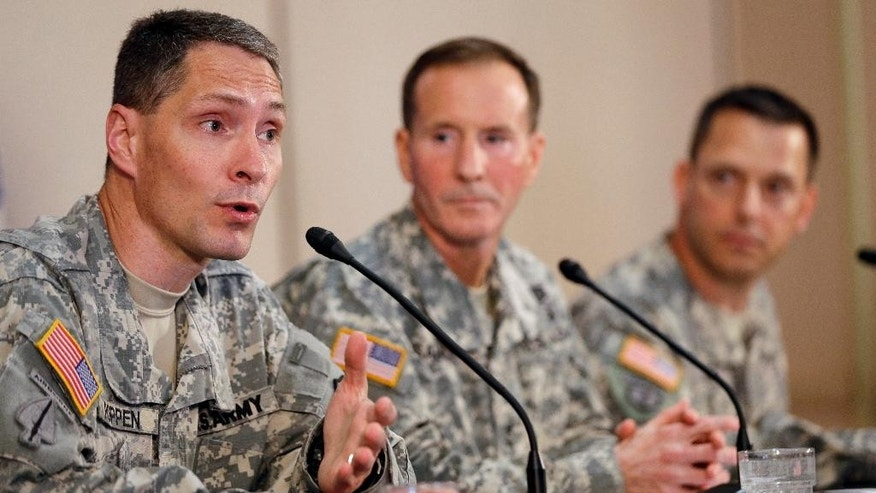 Col. Bradley Poppen, left, answers a question during a news conference regarding Sgt. Bowe Bergdahl, Friday, June 13, 2014, in San Antonio, Texas. Bergdahl, the Army sergeant who has been recovering in Germany after five years as a Taliban captive, returned to the United States early Friday to continue his medical treatment at Brooke Army Medical Center in San Antonio. Joining Poppen are U.S. Army South Commander Maj. Gen. Joseph P. DiSalvo, center, and Col. Ronald Wool. (AP Photo/David J. Phillip)