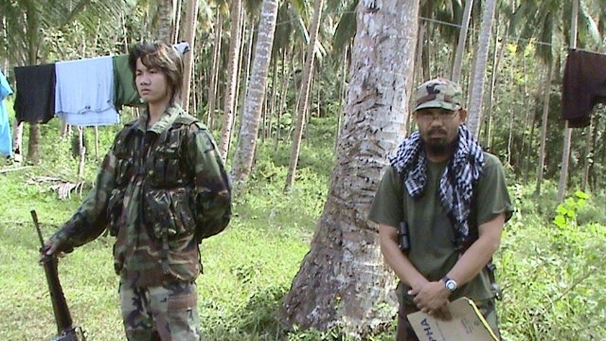 In this undated photo released on Wednesday, June 11, 2014, by the Philippine National Police in Manila, Philippines, Khair Mundos, right,  a top commander of the Abu Sayyaf extremist group who is on the U.S. list of most-wanted terrorists and has once acknowledged receiving al-Qaida funds to finance local bombings, trains his comrades at their camp on Mindanao island in southern Philippines. Philippine security officials said Mundos was arrested in a slum community near Manila's international airport but it was not immediately clear why he was in the capital. The military and police have been hunting him for his alleged involvement in bombings and kidnappings. (AP Photo/Philippine National Police)