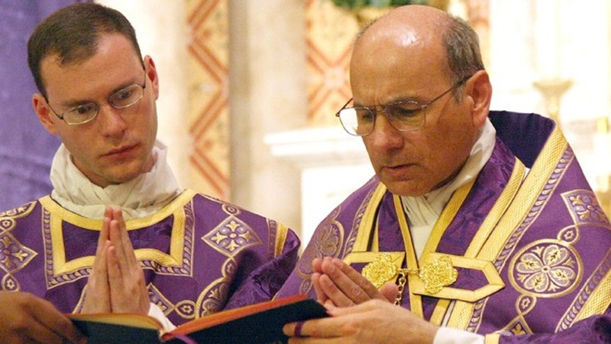 June 11, 2014: In this photo provided by The Catholic Sun, date not known, the Rev. Kenneth Walker, left, and the Rev. Joseph Terra perform a Mass in Phoenix. Walker was killed and Terra was critically injured during a robbery attempt at Mother of Mercy Mission church.