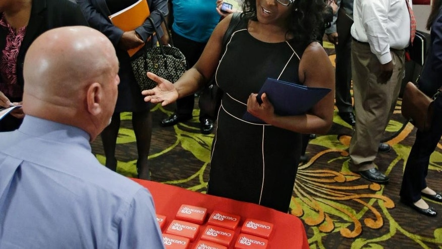 In this Thursday, June 12, 2014 photo, Marsha Lawson talks with a representative from CVS at the Cleveland Career Fair in Independence, Ohio. Optimism among chief executives of large U.S. companies has reached a two-year high, driven by greater optimism about hiring and sales. (AP Photo/Tony Dejak)