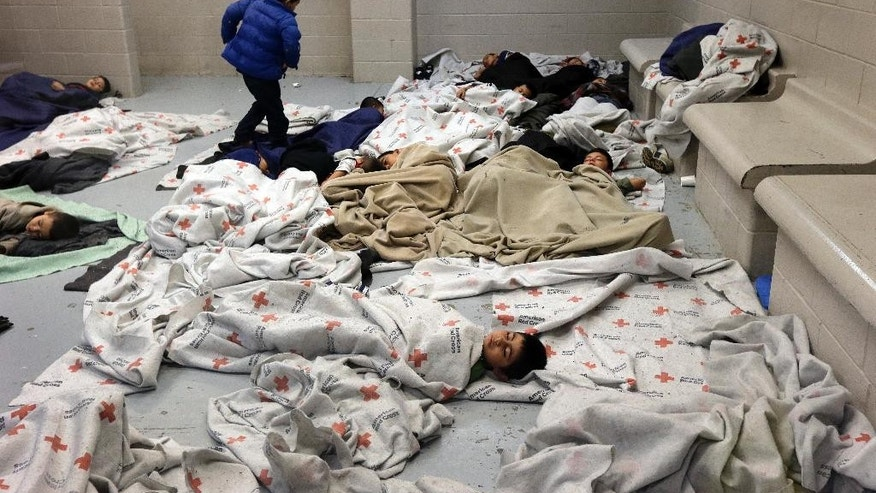 Detainees sleep in a holding cell at a U.S. Customs and Border Protection processing facility, Wednesday, June 18, 2014, in Brownsville,Texas. CPB provided media tours Wednesday of two locations in Brownsville and Nogales, Ariz. that have been central to processing the more than 47,000 unaccompanied children who have entered the country illegally since Oct. 1.  (AP Photo/Eric Gay, Pool)