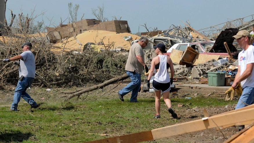 Workers clean up debris in Pilger, Neb., Wednesday, June 18, 2014. Wednesday was the first day volunteers were allowed into town to help with cleanup following Monday's storm, according to the Norfolk Daily News. The storm spawned at least four tornadoes, and killed two people in the Pilger area. (AP Photo/The Norfolk Daily News, Darin Epperly, Pool)