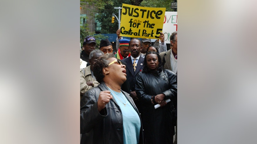 """FILE - In this Oct. 21, 2002 file photo, Dolores Wise, left, whose son Kharey Wise was one of five youths convicted in the 1989 Central Park jogger case, pumps her fist in the air as she sings """"We Shall Overcome"""" at a rally in front of State Supreme Court in New York. On Friday, June 20, 2014, the city has agreed to a $40 million settlement in a civil rights lawsuit filed against police and prosecutors by Kharey Wise and four co-defendants exonerated in the notorious case, a city official said.  (AP Photo/Robert Mecea, File)"""