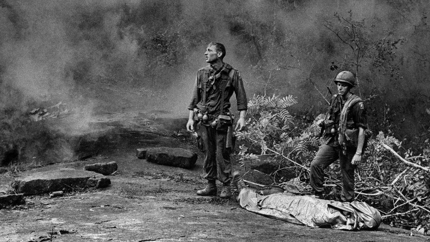 """FILE - In this Aug. 14, 1966 file photo, U.S. Army soldier Ruediger Richter gazes aloft as a helicopter prepares to land to pick up the body of a fallen soldier killed by mortar fire in South Vietnam. Taken by an Army photographer and transmitted worldwide by The Associated Press, the image came to be known widely as """"The Agony of War."""" Richter, a native of Germany who joined the U.S. military after serving in the French Foreign Legion, was part of the 4th Battalion, 503rd Infantry, 173rd Airborne Brigade at the time. He was severely wounded the following year and later developed addictions to alcohol and pain medications while struggling with an undiagnosed case of post-traumatic stress syndrome. After returning to Europe and living in Germany and Hungary with his second wife, Richter moved back to the United States a few years ago received medical care. He now lives in peace in a rural area near Columbus, Georgia. (AP Photo/U.S. Army, Pfc. L. Paul Epley, File)"""