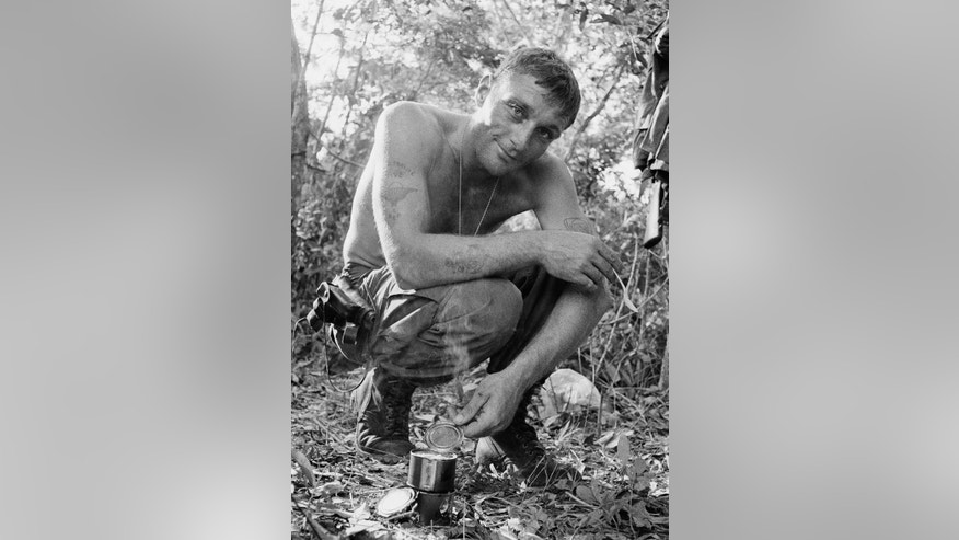"FILE -  In this 1966 file photo, U.S. Army soldier Ruediger Richter, then 25, holds a can of food in a South Vietnamese jungle during his service in the Vietnam War. The picture was taken within days of Richter's image being captured in a photo that came to be known as ""The Agony of War,"" which depicted him directing a helicopter into a landing zone beside the body of a fallen soldier. Richter was severely wounded the following year and then struggled with anger, addictions and post-traumatic stress syndrome for decades, but he now lives in peace in rural southwest Georgia. (AP Photo/Henri Huet, File)"