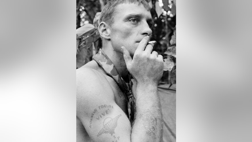 "FILE - In this 1966 file photo, U.S. Army soldier Ruediger Richter puffs on a cigarette in a South Vietnamese jungle during his service in the Vietnam War. The picture of the Berlin native was taken within days of Richter's image being captured in a photo that came to be known as ""The Agony of War."" Richter was severely wounded by a gunshot through the head the following year and then struggled with anger, addictions and post-traumatic stress syndrome for decades. Now a 73-year-old grandfather, Richter lives with his wife in peace in the rural Southern United States near Columbus, Georgia. (AP Photo/Henri Huet, File)"