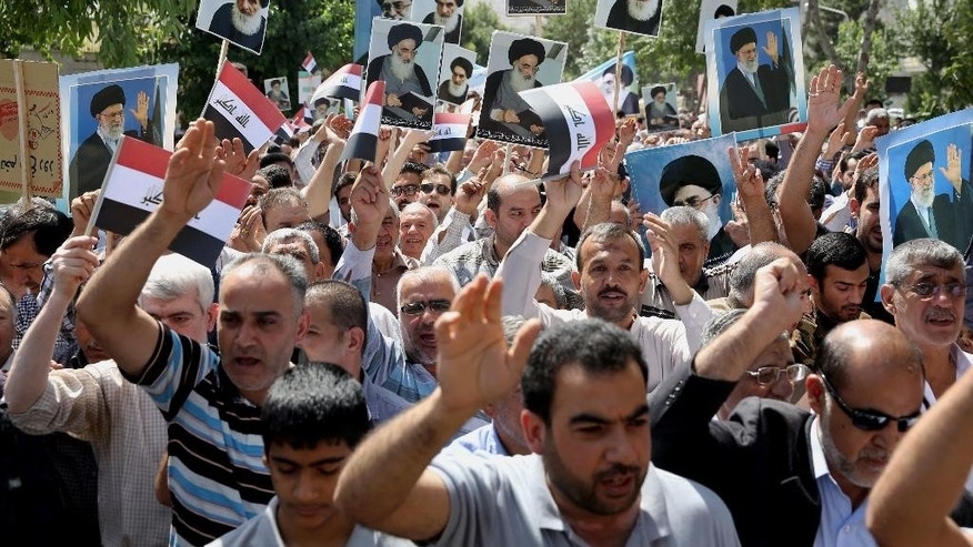 Iraqis living in Iran hold a demonstration against Sunni militants of the al-Qaida-inspired Islamic State of Iraq and the Levant, or ISIL, and to support the Grand Ayatollah Ali al-Sistani, Iraq's top Shiite cleric, shown in the posters, as some of them hold posters of the Iranian Supreme Leader Ayatollah Ali Khamenei, in Tehran, Iran, Friday, June 20, 2014. (AP Photo/Ebrahim Noroozi)