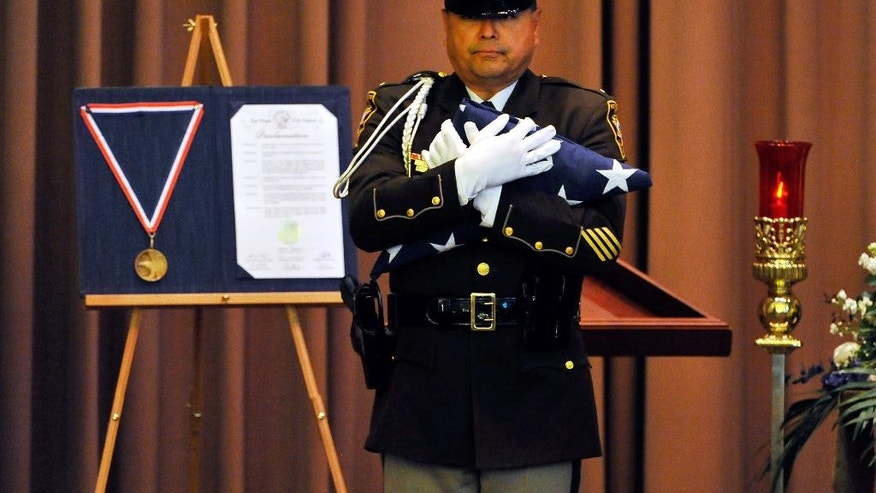 Las Vegas police Lt. Robert Smith, of the honor guard, presents an American flag during a memorial service for Joseph Wilcox at Palm Downtown Mortuary on Sunday, June 22, 2014, in Las Vegas. Wilcox went for his own legal and concealed handgun after a couple killed Officers Igor Soldo and Alyn Beck at a nearby pizza shop and walked into a Wal-Mart, fired a shot in the air, and declared the start of a revolution two weeks ago. (AP Photo/Las Vegas Review-Journal, David Becker, Pool)