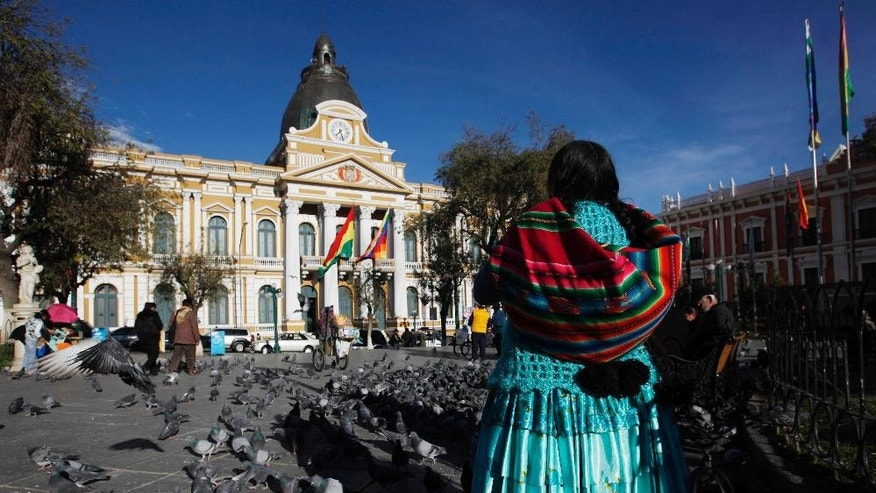 "An Aymara Indian woman looks at the legislative palace in Plaza Murillo in La Paz, Bolivia, Tuesday, June 24, 2014. In the latest symbolic gesture by President Evo Morales government asserting its revolutionary, ''anti-colonial"" nature, Bolivian officials have redone the clock atop Congress. They made its hands turn to the left. (AP Photo/Juan Karita)"
